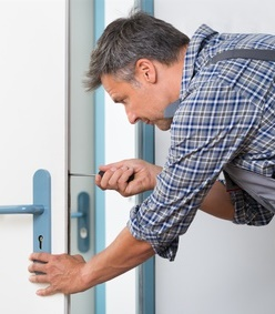 Technician Fixing Lock In Door With Screwdriver